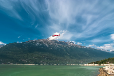 Red and silver helicopter flys over Alaska photo