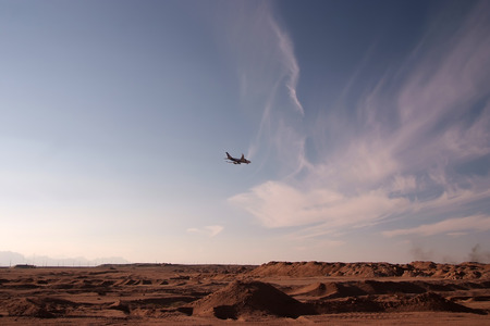 lear: Plane flyes over the desert in the evening Stock Photo