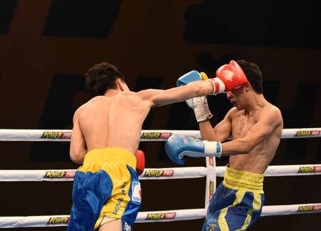 powerfull: Kyiv, UKRAINE - March 20, 2015 : Hu Jianguan (China)  and VUSENALIEV Azat (UA) in the ring during boxing fight Ukraine Otamans vs China Dragons in Palace of Sport in Kiev, Ukraine