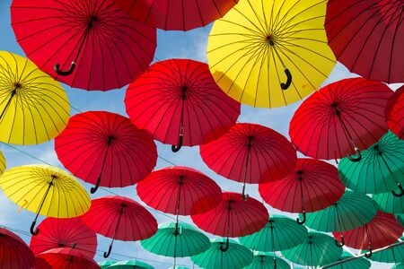 rosso verde: Bright red, green  and yellow umbrellas on cloudy sky background