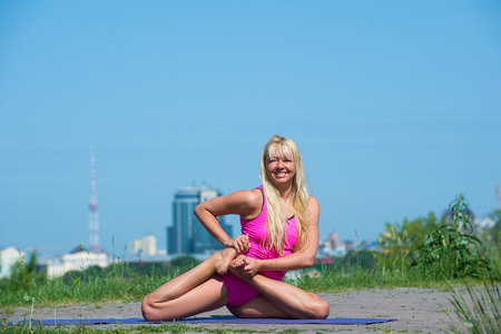 asanas: Preatty young Woman doing yoga asanas in the park at sunny day