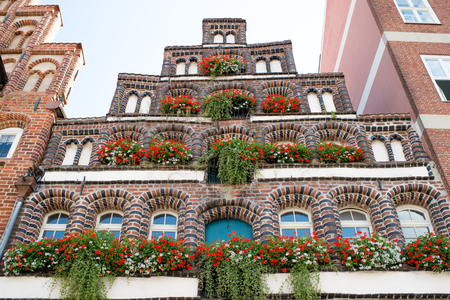 residencial: View on high beautiful old residential brick house with red flower beds near ever window outdoor, horizontal picture