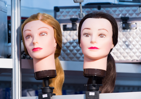 simulating: Two female simulating human faces mannequins for makeup with blonde and brunette hair styles indoor, horizontal picture Stock Photo