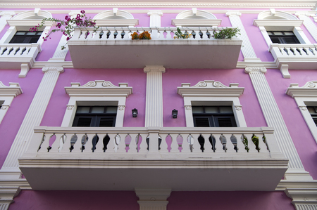 Violet residential building house with white beautiful balcony fence and doors with windows in San Juan, Puerto Rico