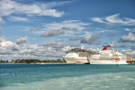 seas: Nassau, Bahamas - January 07, 2016: Cruise ship Carnival Pride of Carnival Cruise Lines and luxury cruise ship Seven Seas Navigator of Regent Seven Seas Cruises standing in bay sunny day