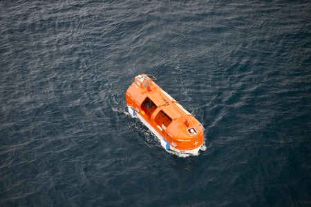 orange nassau: Seven Seas Navigator, st .Barts - November 19, 2015: Orange cruise ship life boat sailing next to st .Barts on dark water