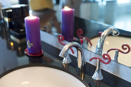 Closeup view of comfortable bath room with white and chrome sink and violet candle near clean reflecting mirror with no people indoor, horizontal picture Stock Photo