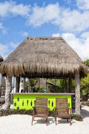 Beach Bar en una playa tropical con el cielo azul y la arena día soleado.