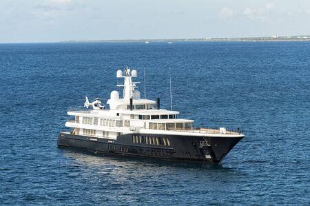 romana: Yacht white and black color around blue ocean water in La Romana, Dominican Republic