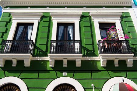 Grüne Wohngebäude Haus mit schwarzem Eisen Balkon Zaun und Türen mit Fenstern sonnigen Tag