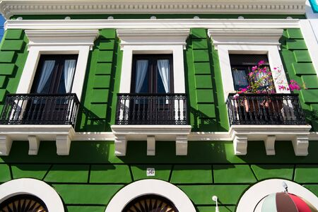 Green residential building house with black iron balcony fence and doors with windows sunny day