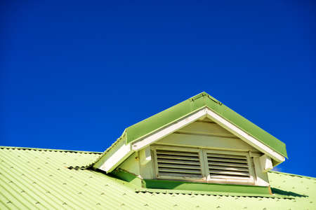 housetop: Light green building roof with ventilation on blue sky background, copy space Stock Photo