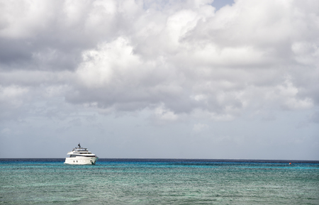 cloudy moody: Yacht on water and grey cloudy sky in moody weather outdoor on horizon line background, copy space Stock Photo
