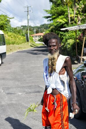 messy hair: Castries, st.Lucia-November 26, 2015: homeless african american man with messy hair and long beard holding money and palm leaf suuny day outdoor on road