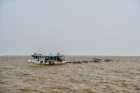 río amazonas: r�o Amazonas, Brasil-2 de diciembre de 2015: Remolcador vela de color gris agua sucia de color marr�n con muchos peque�os barcos de madera en el fondo de cielo cambiante