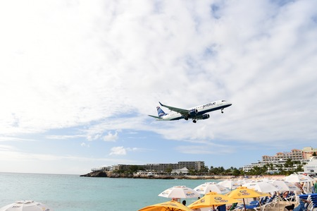 juliana: ST. MAARTEN, ANTILLES, Netherlands - January 24, 2016: JetBlue plane lands on Juliana International Airport in Netherlands Antilles above water and beach with umbrellas