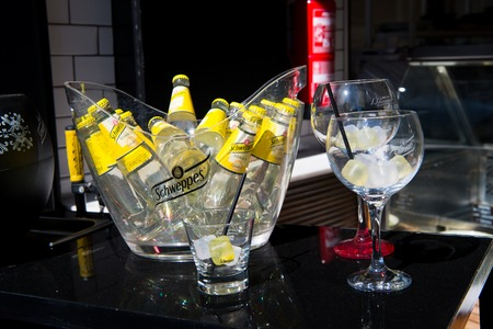 Key west, Fl, USA - March 30, 2016: Schweppes Tonic Water bottles yellow color in glass with cold ice cubes on table near bocals of lemon beverage with drinking straw Editorial
