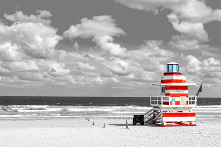 guard house: modern life guard house or beach patrol tower white and red color on ocean or sea water coast with sand and cloudy sky, copy space, black and white