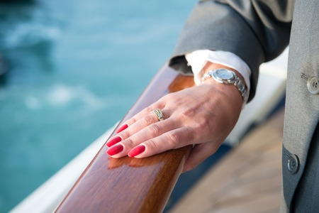 lady hand: Female hand and wrist-watch with red manicure and golden ring on finger with diamonds near water
