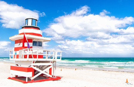 florida house: Miami, South Beach, Florida, lifeguard house in a typical colorful Art Deco style on cloudy day with blue sky and Atlantic Ocean in background, world famous travel location