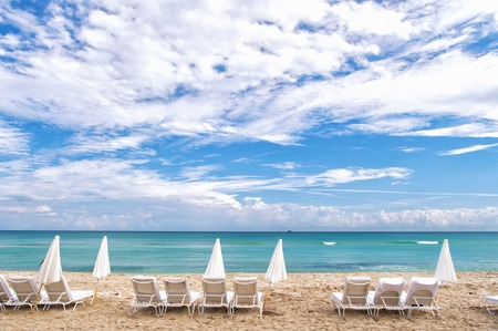 south miami: White summer deck chairs and closed umbrellas standing in line on empty ocean coast with sand and cloudy blue sky in South Beach, Miami, Florida