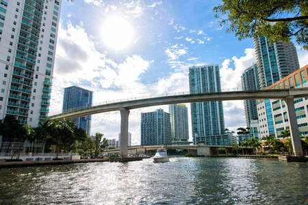 ander: Downtown Miami along the Miami River inlet with Brickell Key in the background and yacht cruising ander the bridge