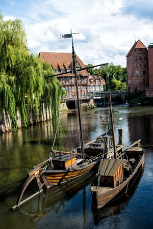 wooden boats floating on river water near house buildings and tree with blue cloudy sky outdoor at Luneburg, Germany Stock Photo
