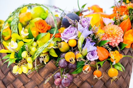 winter cherry: beautiful decoration floral composition or bouquet of seasonal fruits grapes dogrose rosehip and physalis or winter cherry with many flowers orange violet and green color in straw basket Stock Photo