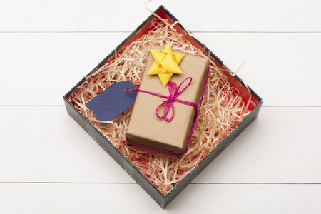 chirstmas: Colorful Christmas or New Year decoration with Christmas box, gift with rose thread, golden yellow bow and blue tag inside on vintage white background