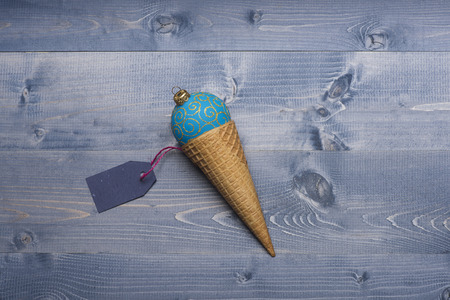 blue ball: Decorated Christmas gift with light blue christmas ball, ice cream cone and blue tag with rose thread on vintage wooden background.