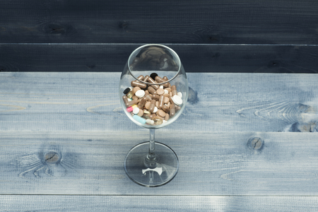 Medical capsules and tablets inside wine glass on vintage wooden background. Side view Stock Photo