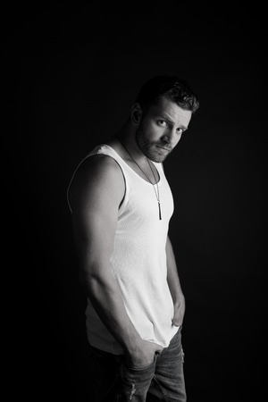 macho: young handsome bearded man macho with muscular hands and beard on serious face in white vest posing in studio, black and white