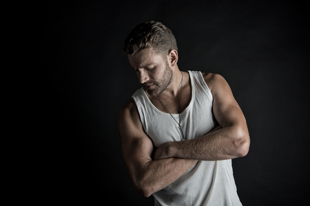 macho: young handsome bearded man macho with muscular hands and beard on serious face in white vest posing in studio on black background Stock Photo