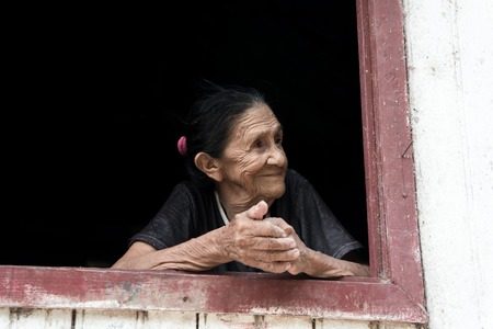 mulatto woman: Boca de Valeria, Brazil - December 03, 2015: old mature mulatto woman with kind smiling face holding hands together standing in wooden window brown and white color looking outdoor Editorial