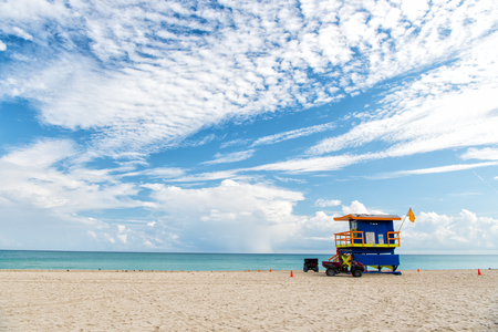 South Beach, Miami, Florida, lifeguard house in a colorful Art Deco style on cloudy blue sky and Atlantic Ocean in background, world famous travel location