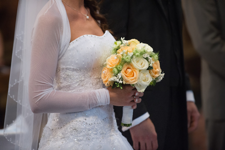 Beautiful wedding roses bouquet in hands of the bride