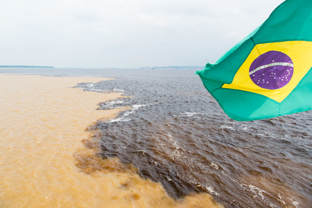 trip over: water meeting in brazil -amazon river with rio del negro clean and dirty river water with different streams