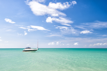 Attractive bright view of exotic colorful beautiful marine beach of Antigua St. Johns with boat on blue water and sky with small clouds in sunny weather outdoor on natural background, horizontal photo Stock Photo