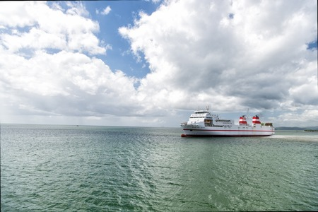 inshore: Port of spain, Trinidad and Tobago - November 28, 2015: modern ship vessel floats in blue sea inshore on cloudy sky on seascape background