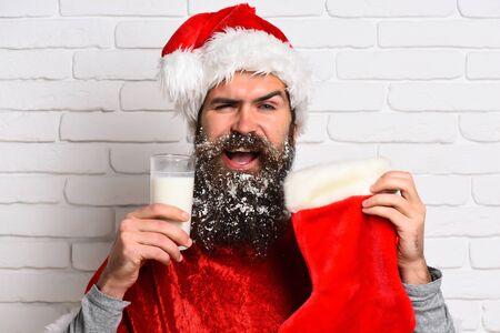 milk mustache: handsome bearded man with stylish mustache and long snowy beard on smiling face holding glass of milk with christmas sock in red santa suit on white brick wall background