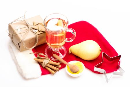 vin chaud: Un verre de délicieux glintwein ou chaud miel vin chaud, cuillère en bois, poire, cadeau enveloppé dans du papier kraft avec un arc, des flocons de neige, étoile d'argent et le Père Noël chaussette rouge isolé sur fond blanc Banque d'images