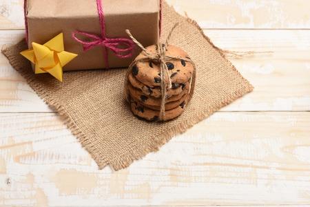 servilleta de papel: galletas de avena con chocolate, regalo con hilo de color rosa, amarillo arco y servilleta punto en el fondo de madera de época