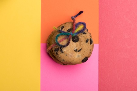 string top: Chocolate chip cookies tied with rainbow string on colorful background, top view