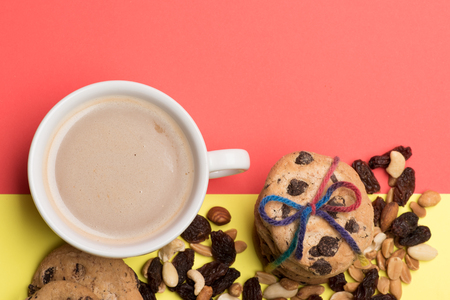 string top: White cup of coffee with milk or cappuccino with chocolate chip cookies tied with rainbow string and different types of nuts on colorful red yellow background, top view Stock Photo