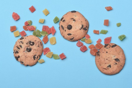 bonbons: Set of chocolate chip cookies with colorful marmalade or jelly candies on light blue background