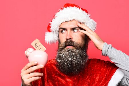 handsome bearded man with stylish mustache and long snowy beard on serious face holding pink pig piggy bank and forgot something in red santa suit on studio background