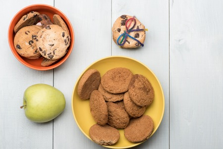 string top: Chocolate chip cookies with rainbow string and oatmeal cookies in orange yellow bowls and fresh green apple on white vintage wooden background, top view