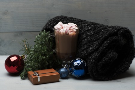 red christmas ball: Cacao or chocolate with marshmallows in glass, scarf, christmas balls, pine branch and coffee cup, set of christmas decoration on wooden background. Side view