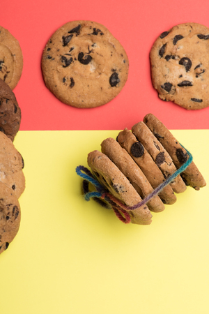 string top: Chocolate chip cookies tied with rainbow string on colorful red yellow background, top view