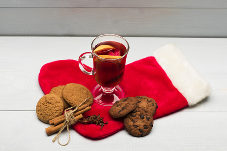 vin chaud: Glass of delicious glintwein or mulled hot wine, cinnamon, thread, anise, oatmeal cookies and Santa Claus red sock on vintage wooden background Banque d'images